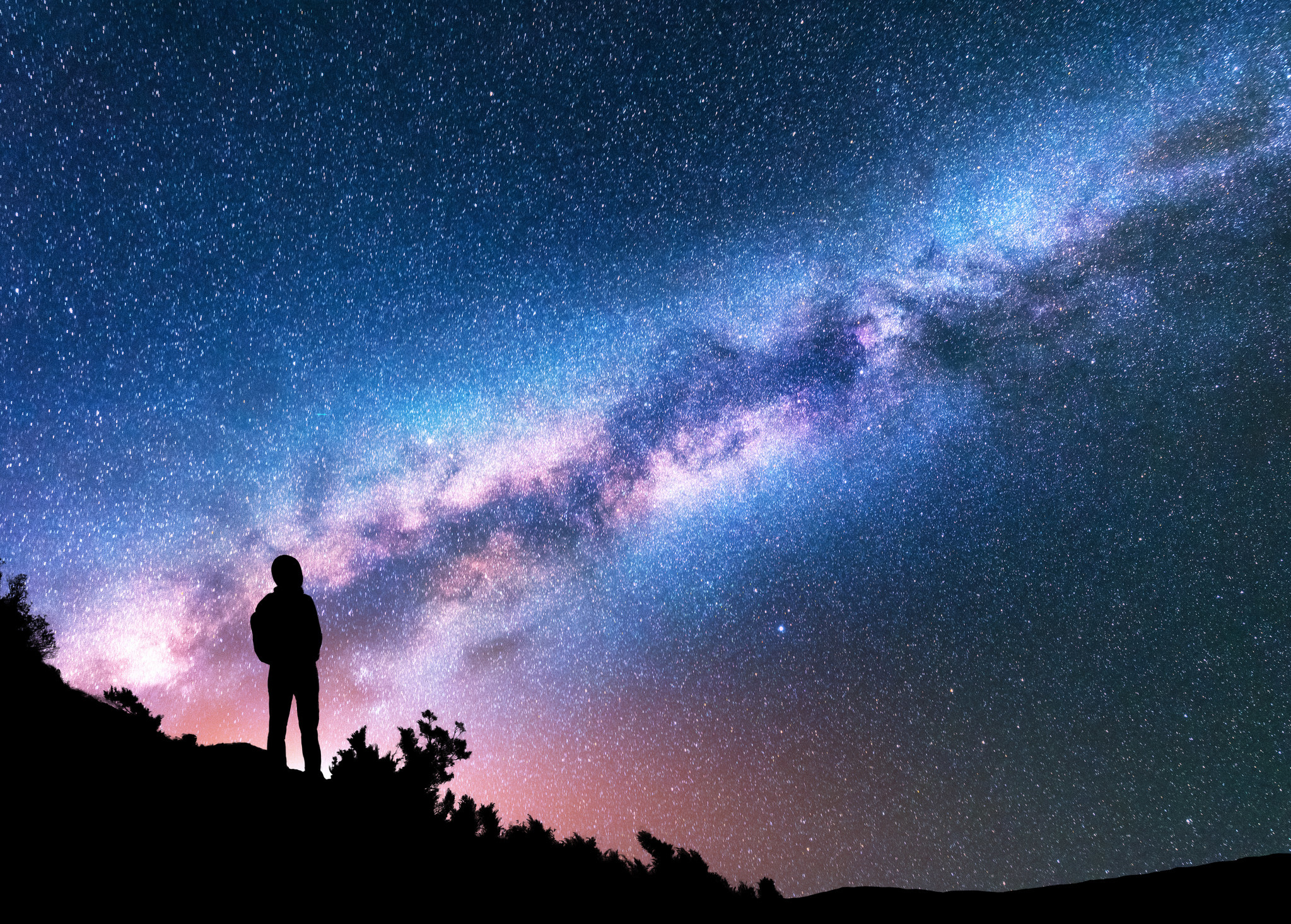 photo of a silhouette of a man with a backpack staring at the milky way stargaze at night