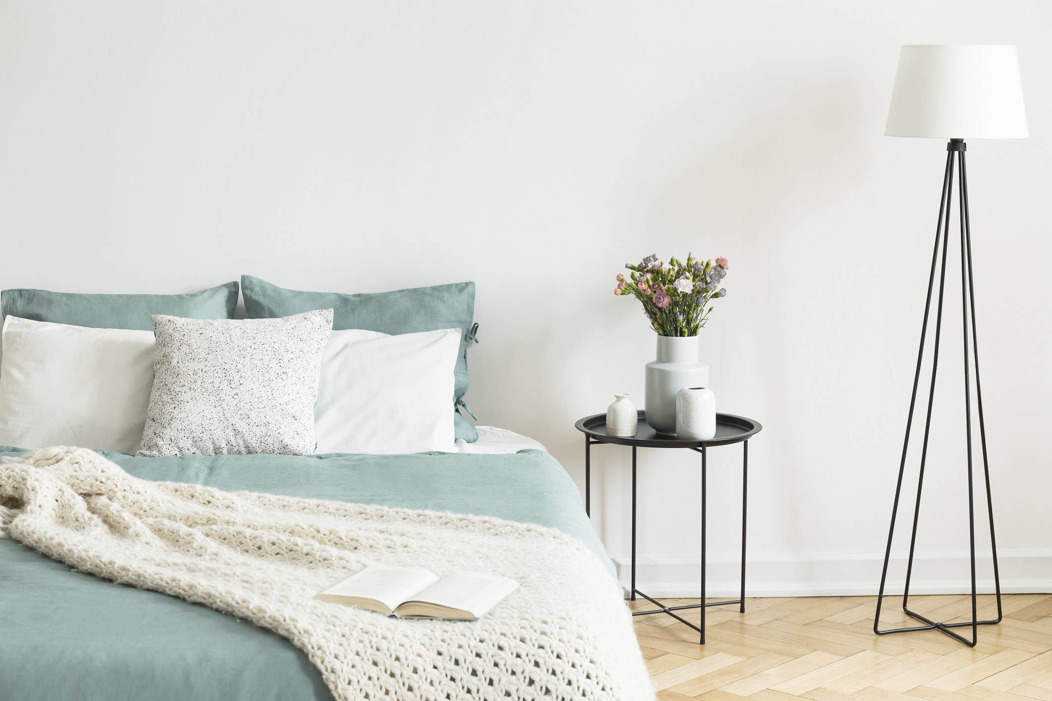 photo of a room that is neatly put together, on the left is a bed with a blue sheet set and quilt with a white throw hanging on the edge with a book on top of it, in the middle is a stand for flowers and on the left side is a standing light