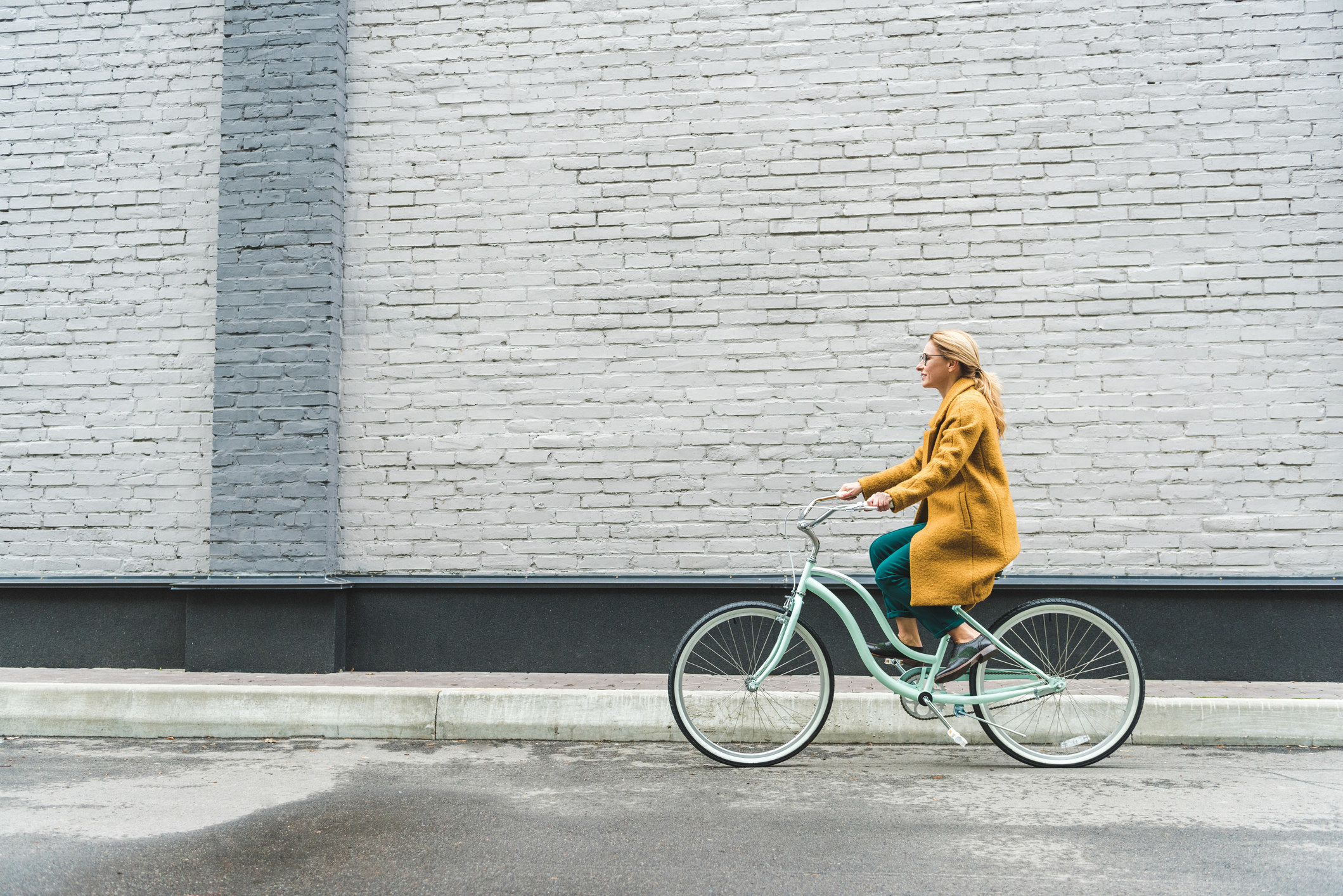 photo of a woman riding a blue bike while wearing green pants and a yellow long jacket, she has blonde straight hair and is wearing glasses
