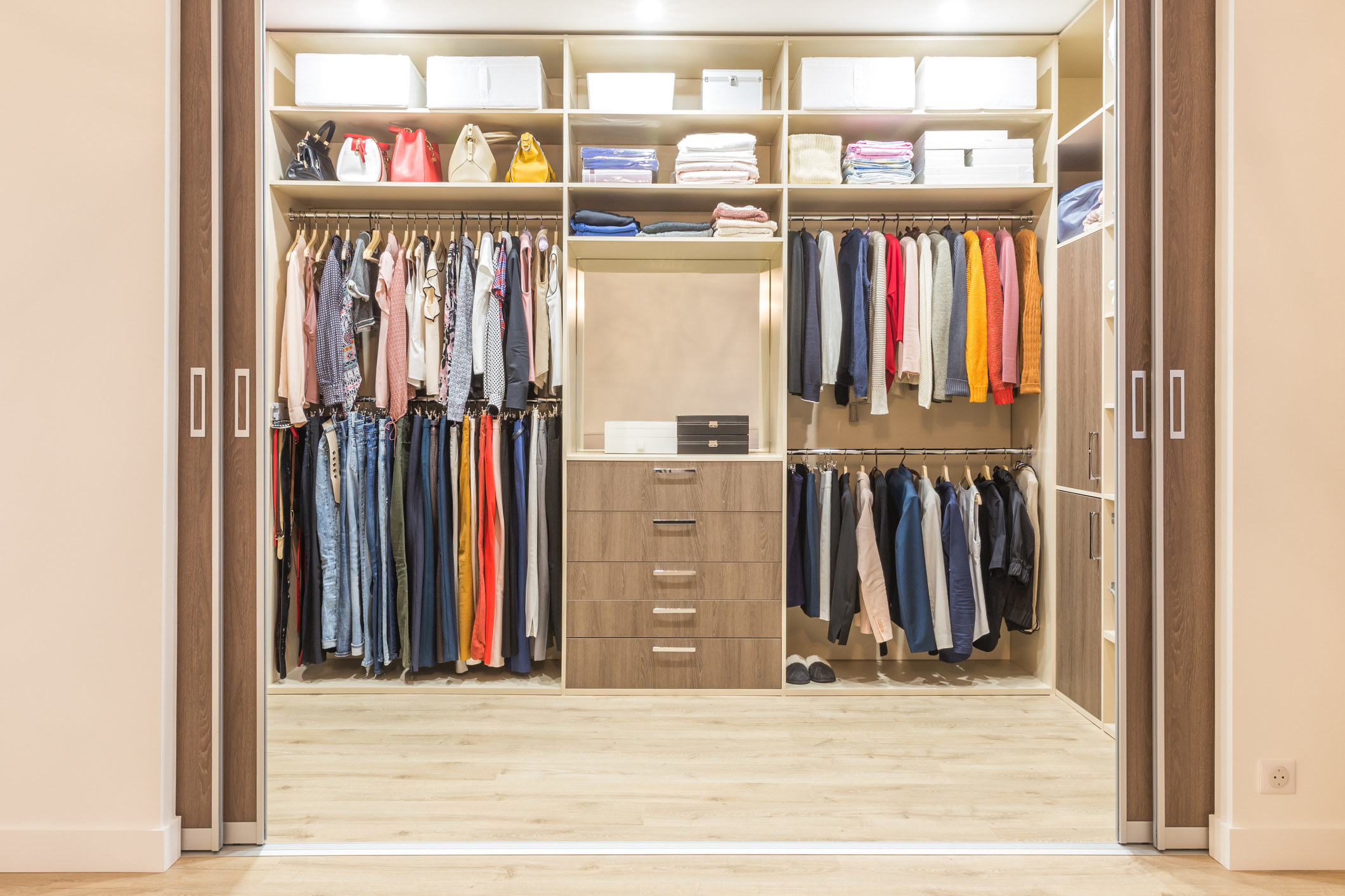 photo of a large walk in closet in an apartment with the doors to the side, the walk in closet is white, brown and beige with clothes hanging neatly, above the hangers are bags, folded clothes and white storage boxes