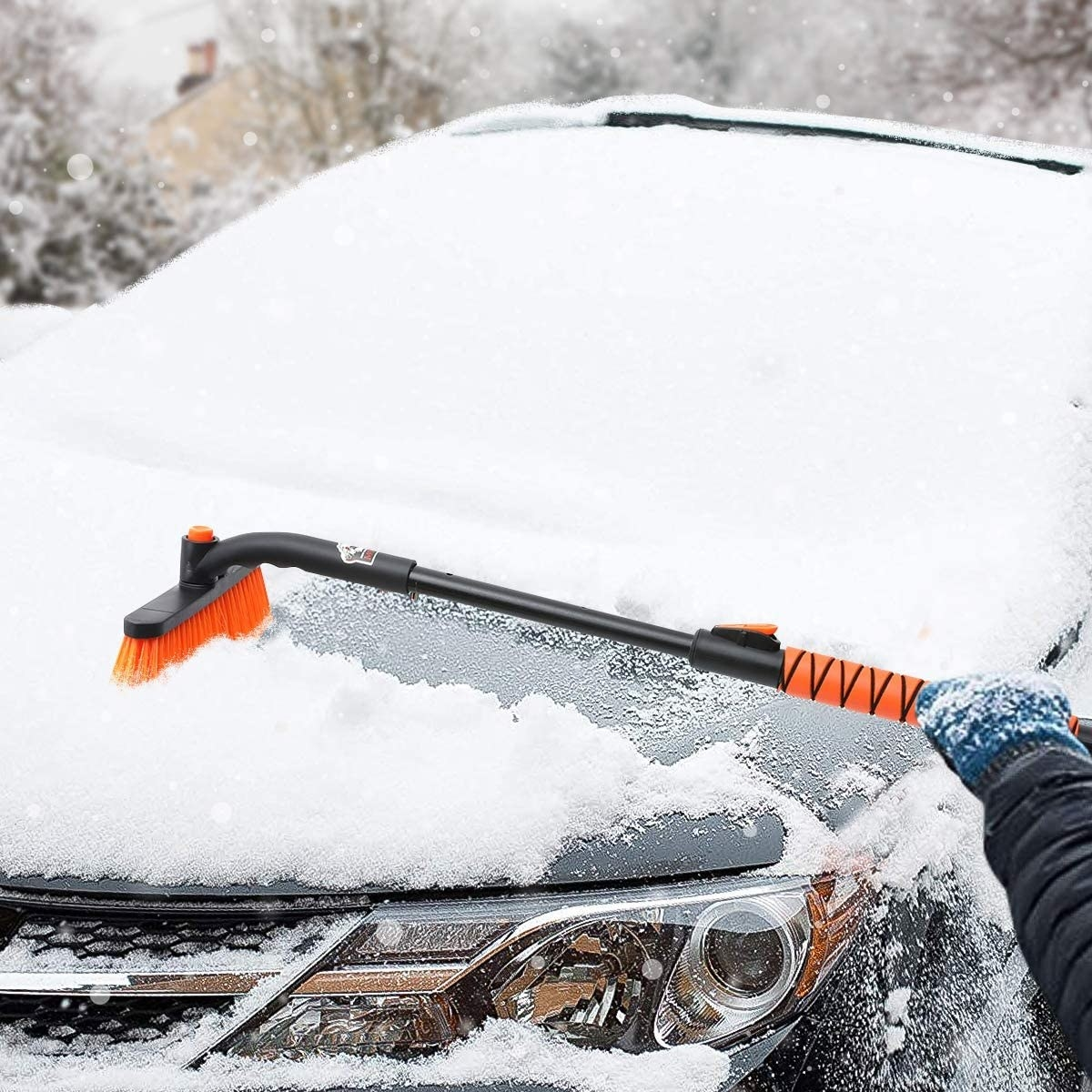 A model using the snow brush on a snowy mid-sized car