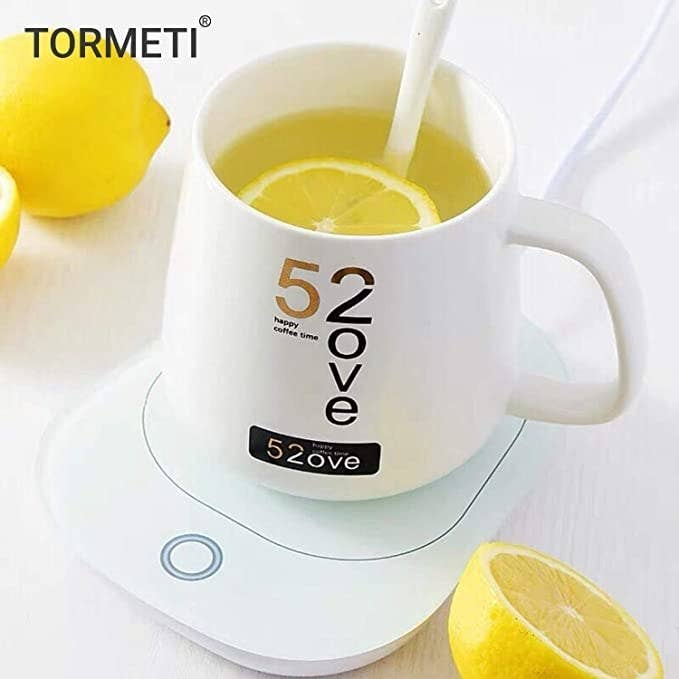 White mug with some green tea and lemons in it standing on the mug warmer.