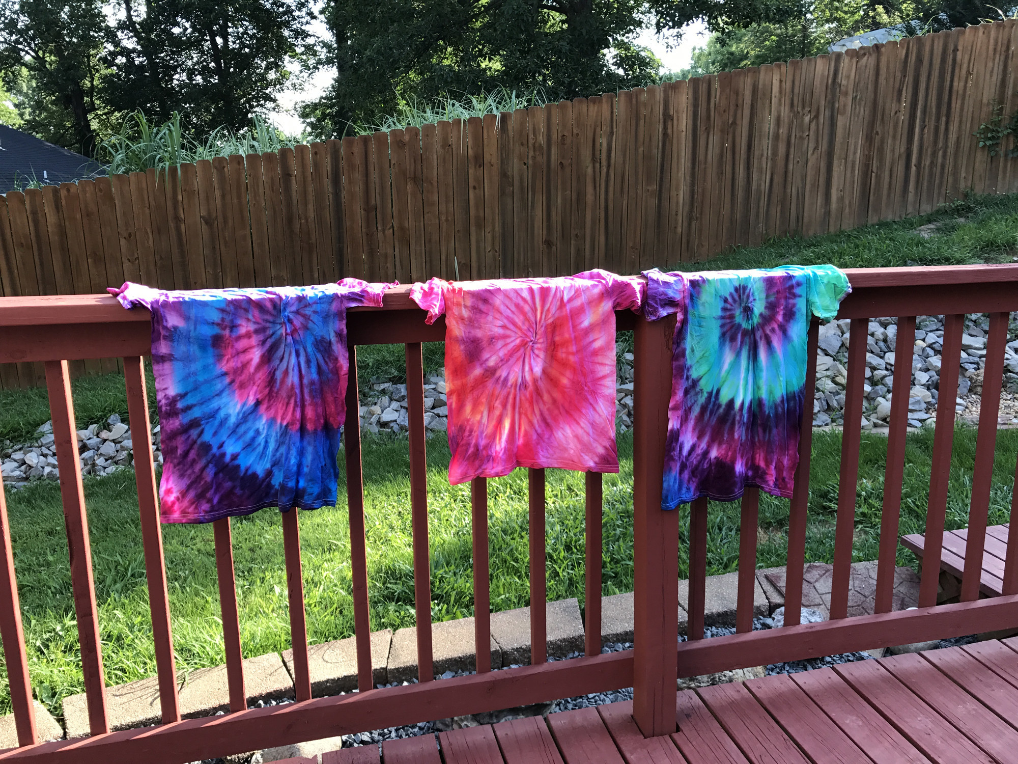 photo showing three tie dyed shirts drying outside in a backyard, one shirt is painted pink, purple, blue and navy, the second shirt is pink, purple and orange, the third is turquoise, purple, navy and blue