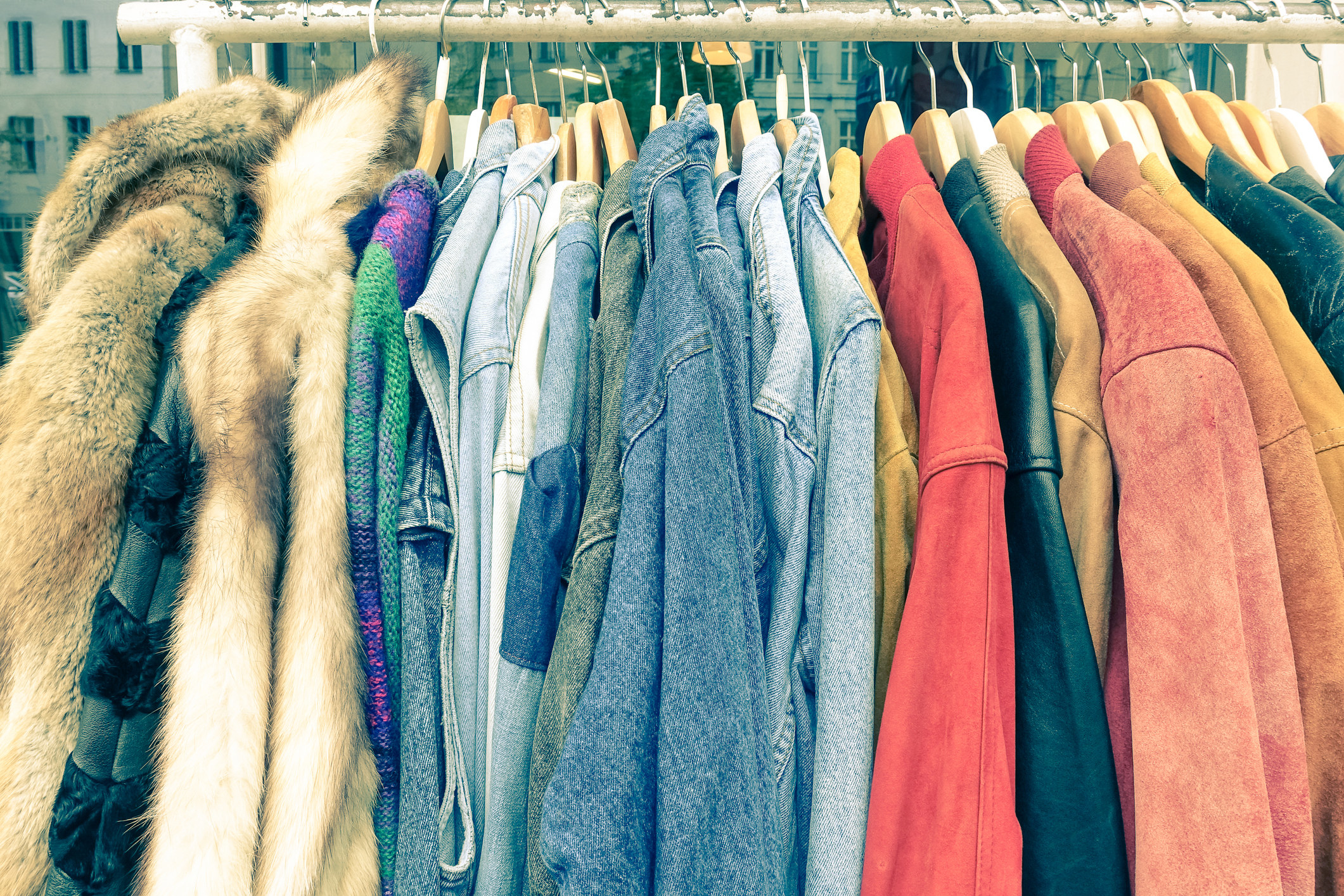 photo of a up-close hanging wrack of jackets, the jackets are a mix of fur and jean jackets