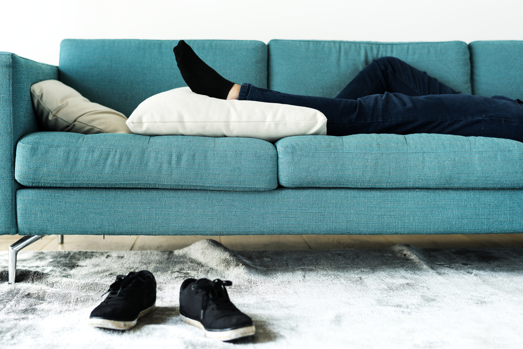 photo of someones legs laid on a blue couch with their sneakers in front of a carpet, their legs are resting on a white pillow and they are wearing dark blue jeans