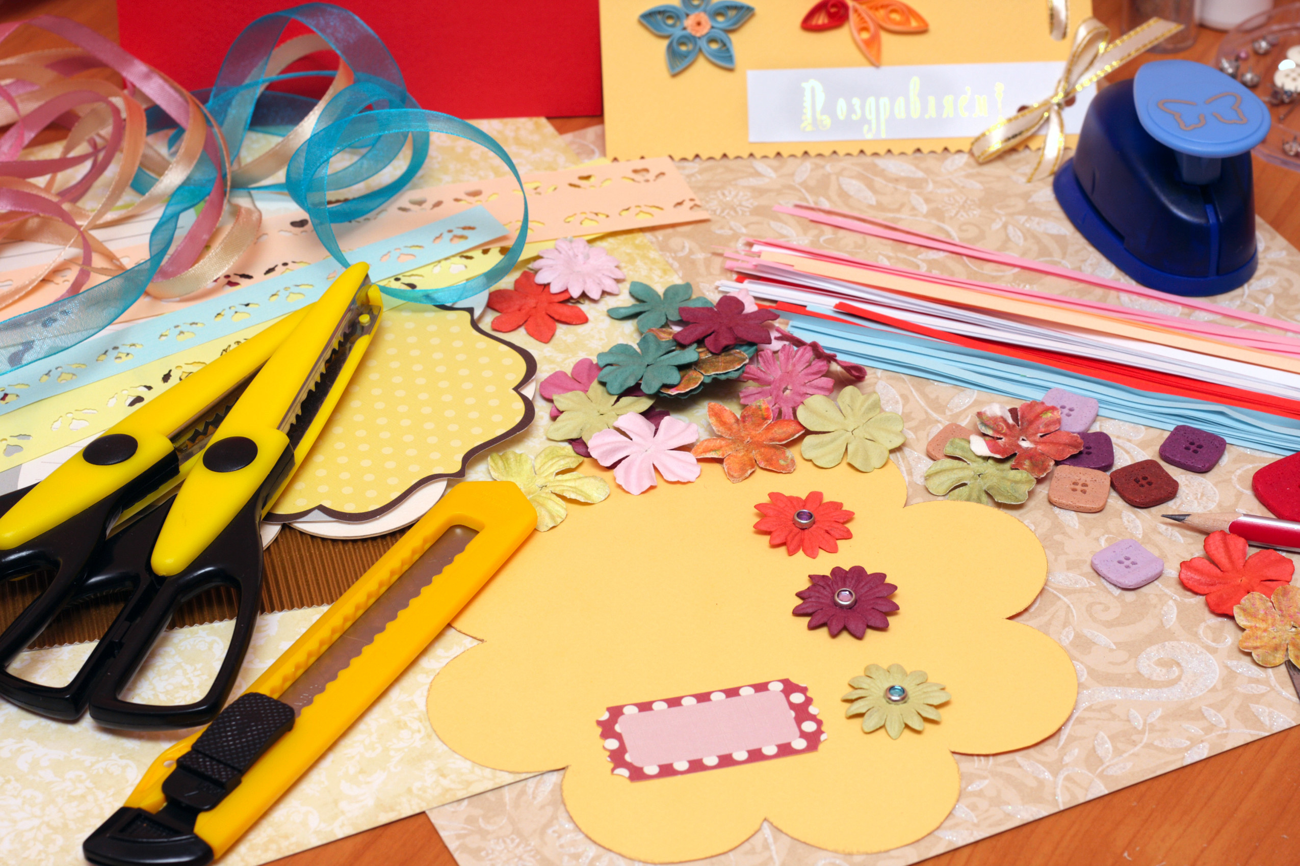 photo of a diy arts and craft table with paper shaped like flowers and accessories to be added to the paper shaped like a flower