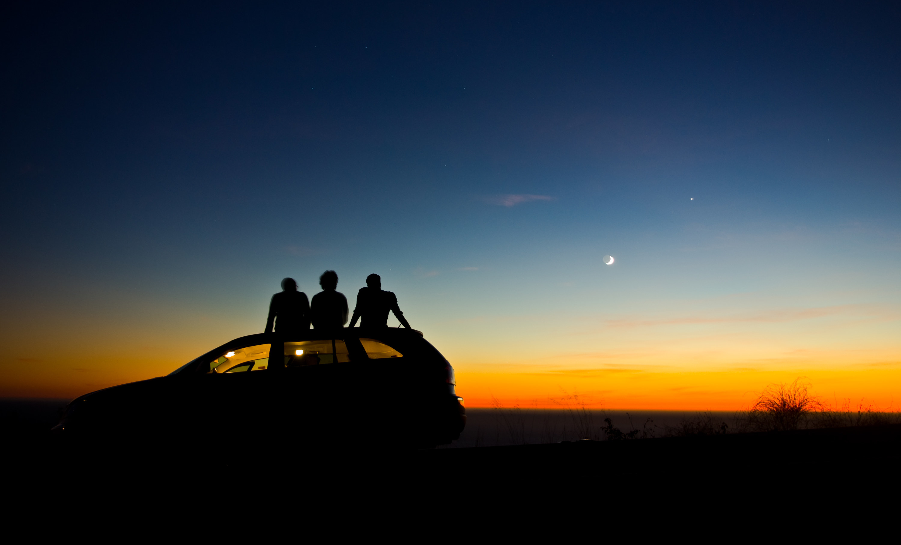 photo of the sunsetting and the moon appearing while on the left is a car with three people sitting on top of the roof of the car while watching the sunset, the sky is dark blue, blue, orange