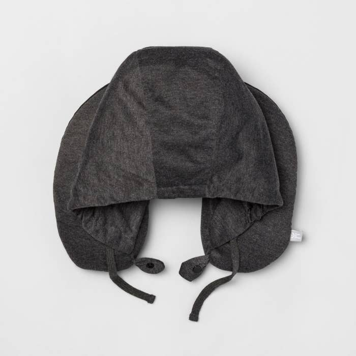 The U-shaped pillow in grey, with a hood sewn to the inner rim of the U, and adjustable straps at the bottom to tighten the hood