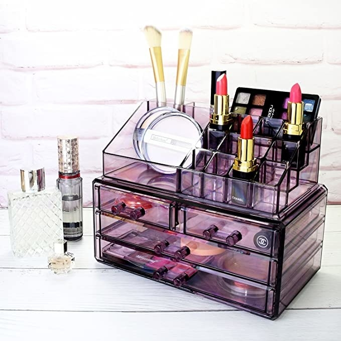 The purple Ikee Design Jewelry & Cosmetic Storage Display Boxes filled with makeup and propped next to three bottles of perfume