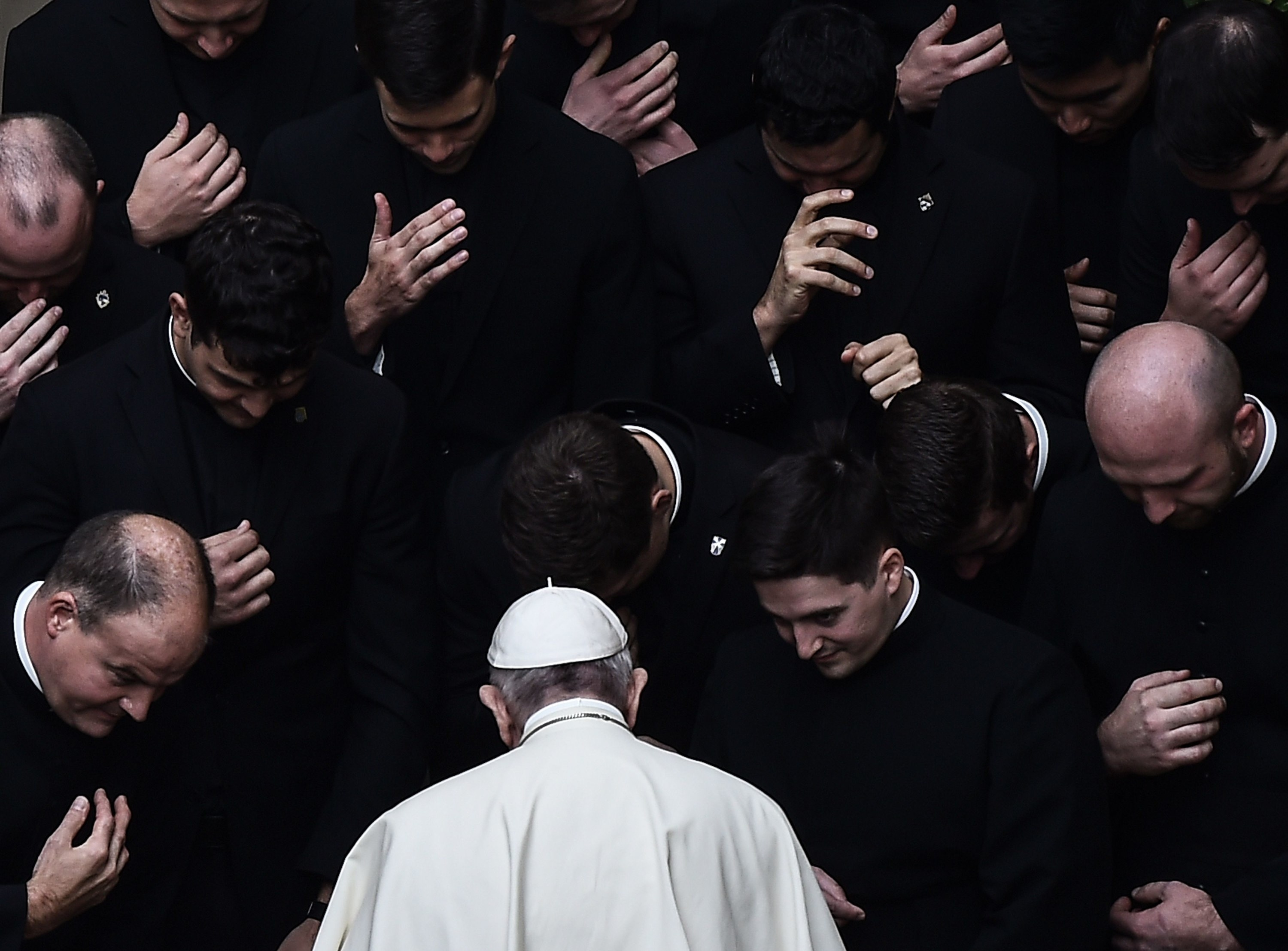 The pope, dressed in white, is surrounded by priests, dressed in black