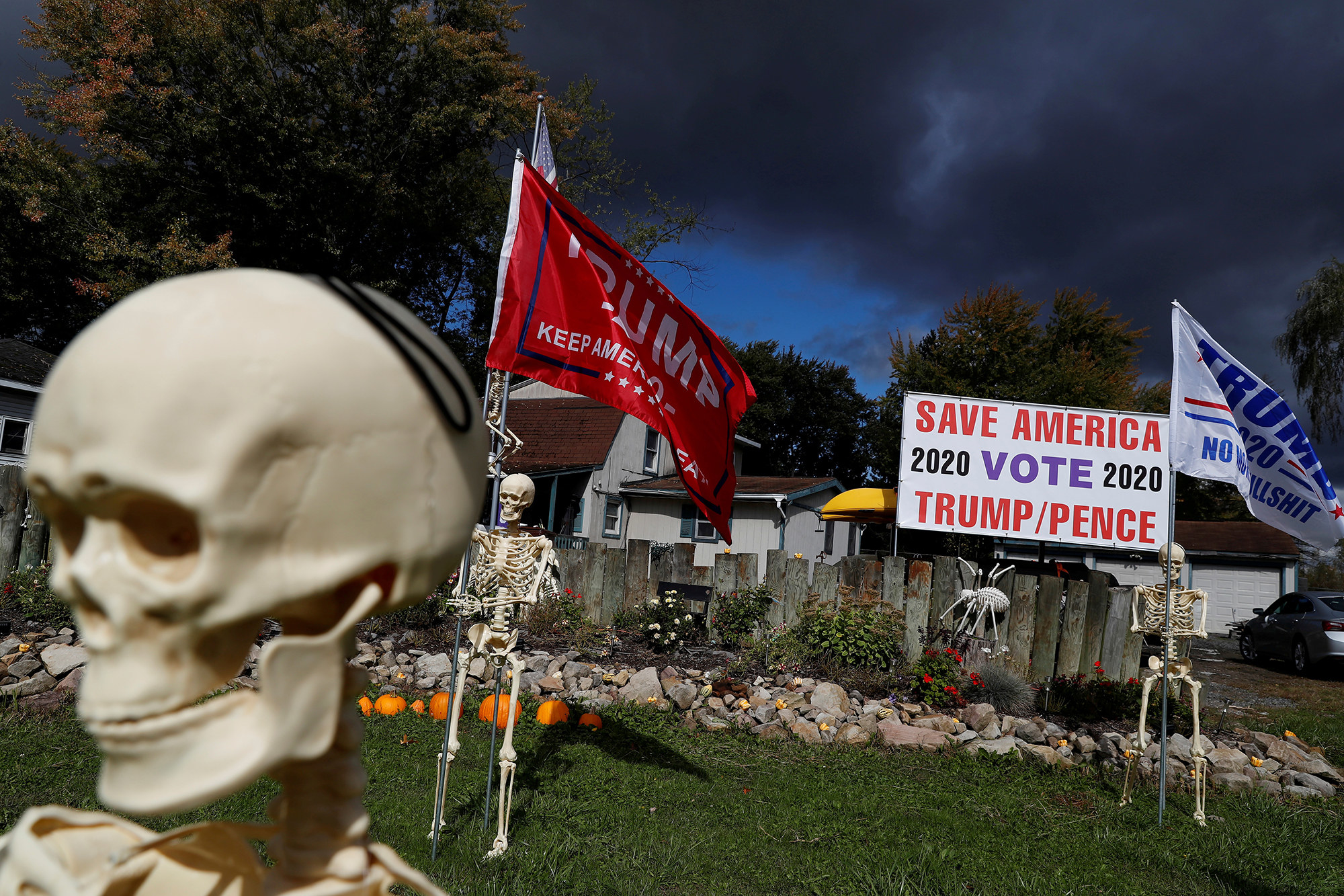 "A skeleton holds a ""Trump: Keep America Great"" flag near a sign that reads ""Save America, vote Trump/Pence"""