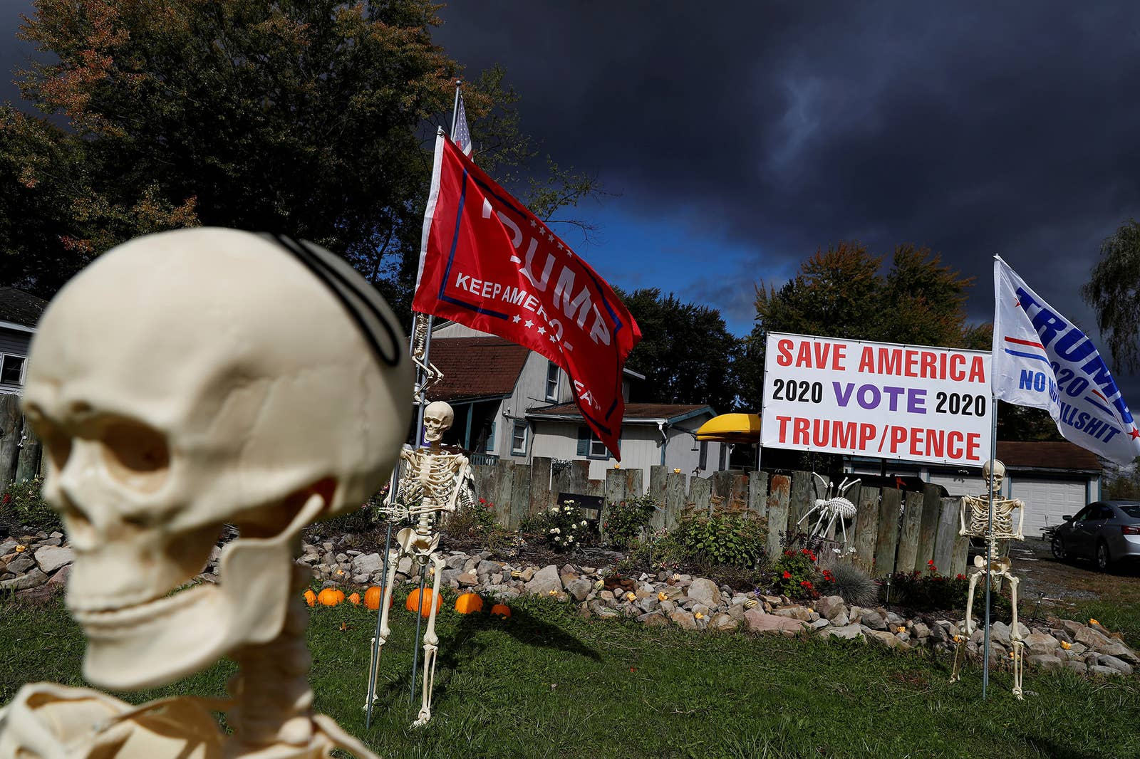 """A skeleton holds a """"Trump: Keep America Great"""" flag near a sign that reads """"Save America, vote Trump/Pence"""""""