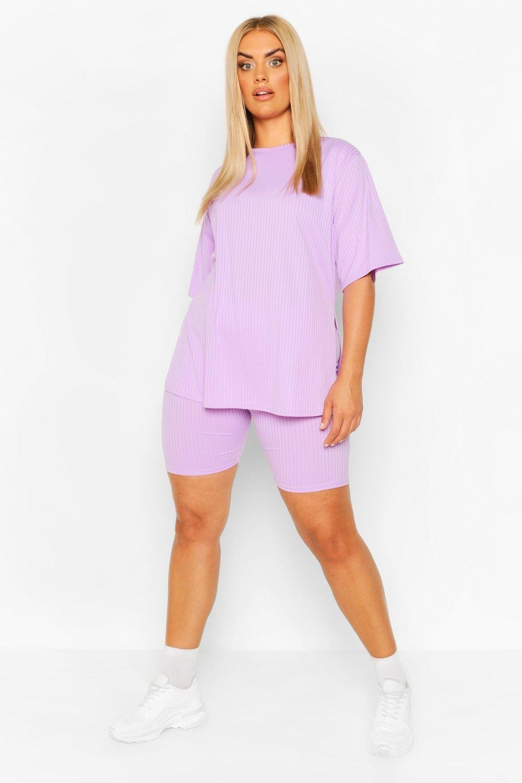 Model wears light purple side-split top with bike shorts set and white sneakers