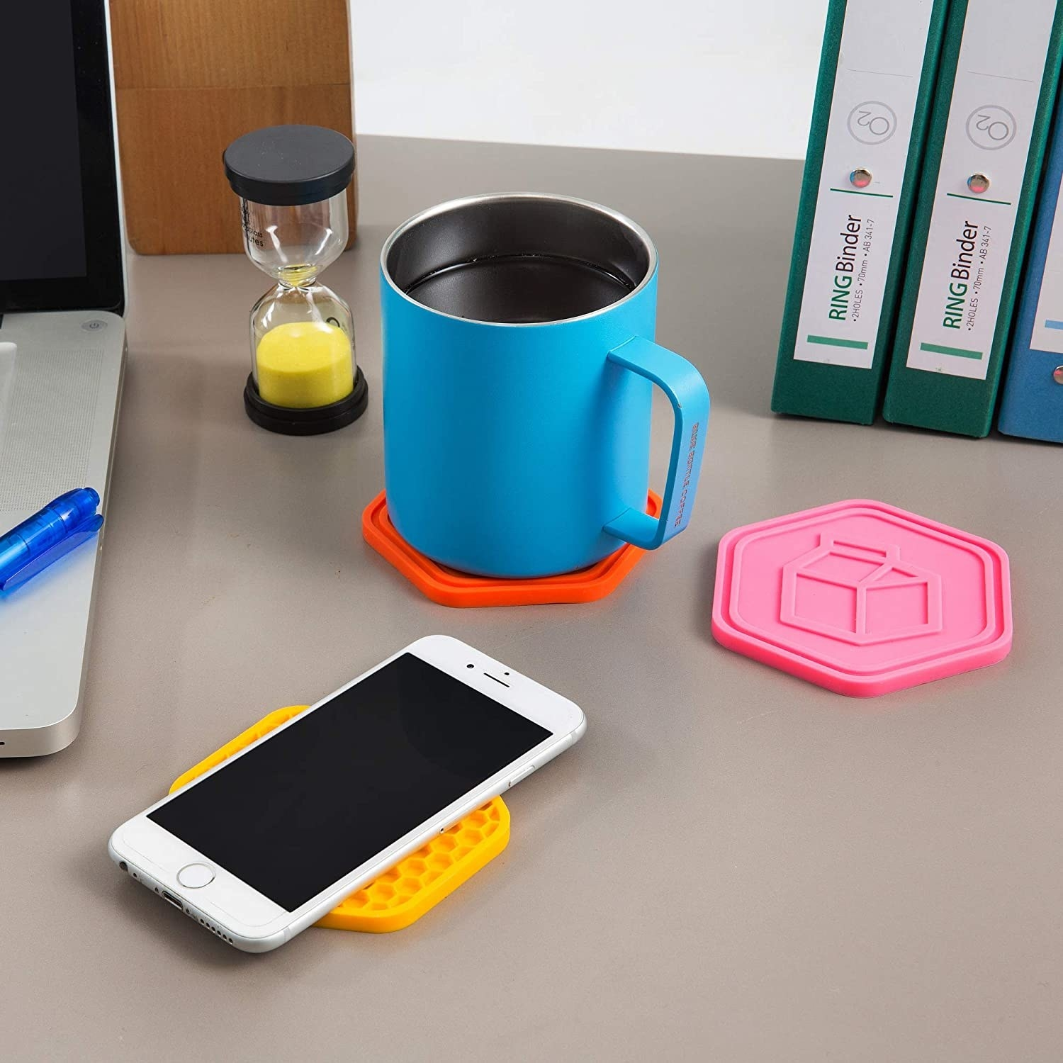 A trio of coasters on a desk, topped with a mug and a cell phone