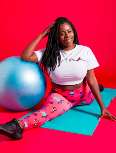Model wears coral leggings with colorful print of women doing yoga and a matching white crop top