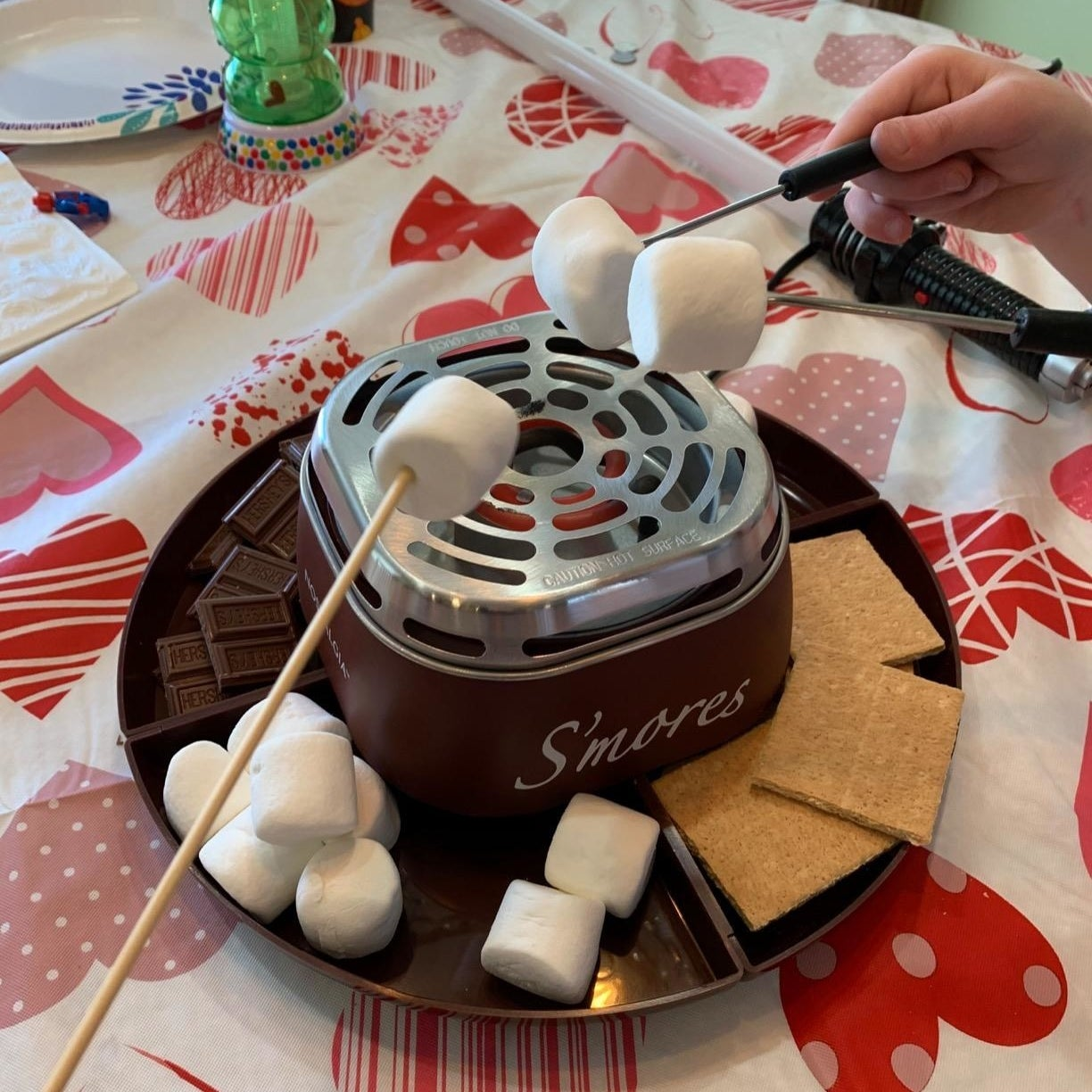 A reviewer's s'mores maker in use with marshmallows, chocolate, and graham crackers in the tray