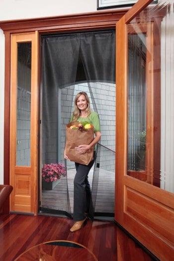 Model easily walking through the instant screen door with hands full of groceries
