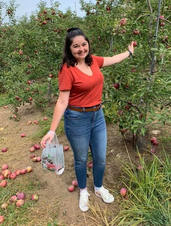buzzfeed editor apple picking in an orange v-neck tee tucked into jeans