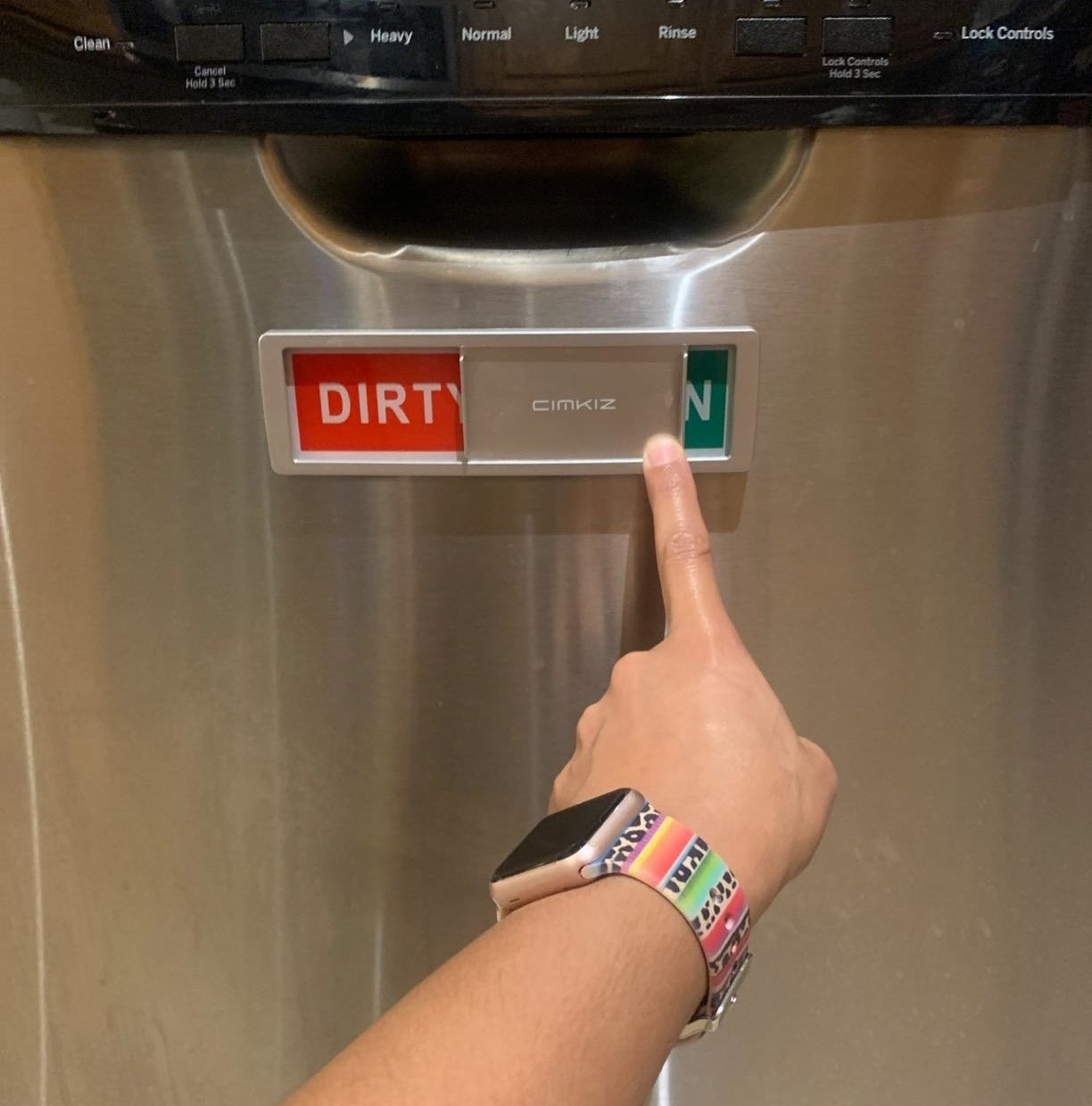 A person touching the dishwasher magnet