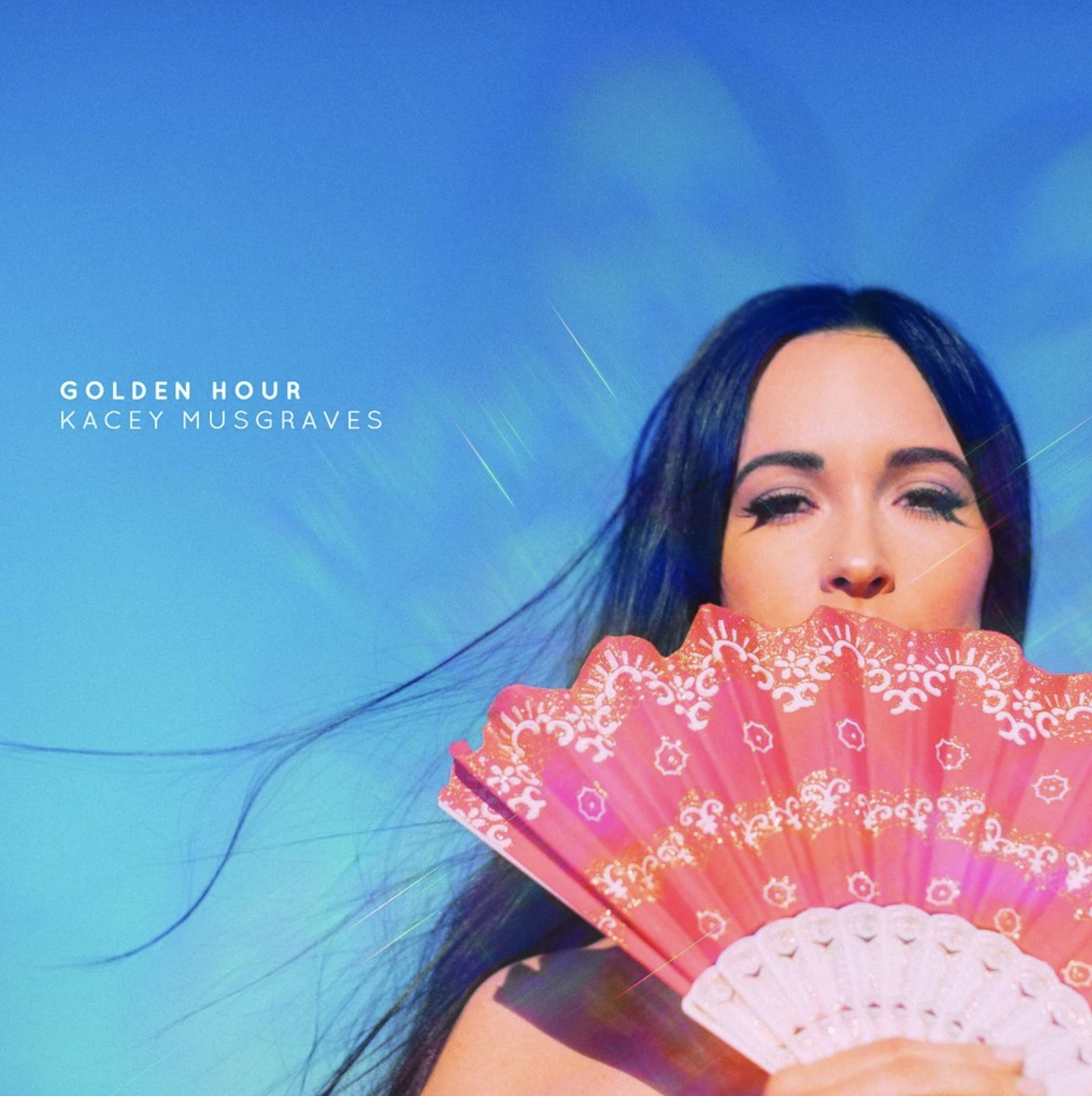 Kacey Musgraves with her hair blowing in the wind and a fan in front of her face.