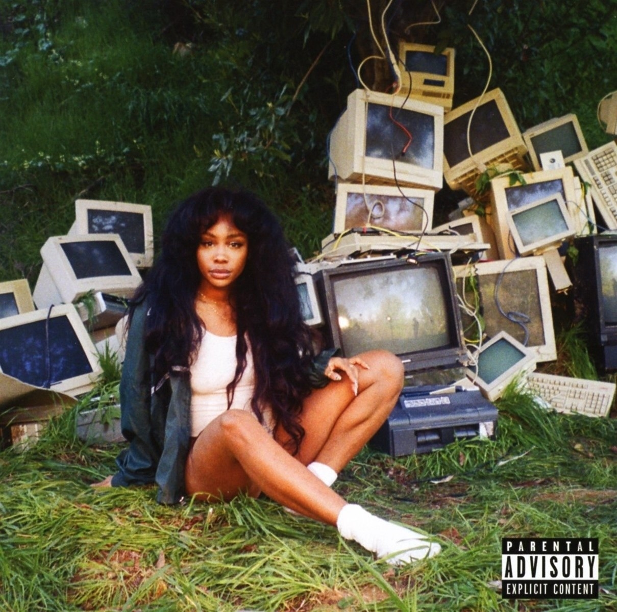 SZA sitting in the grass surrounded by a slew of broken computers.