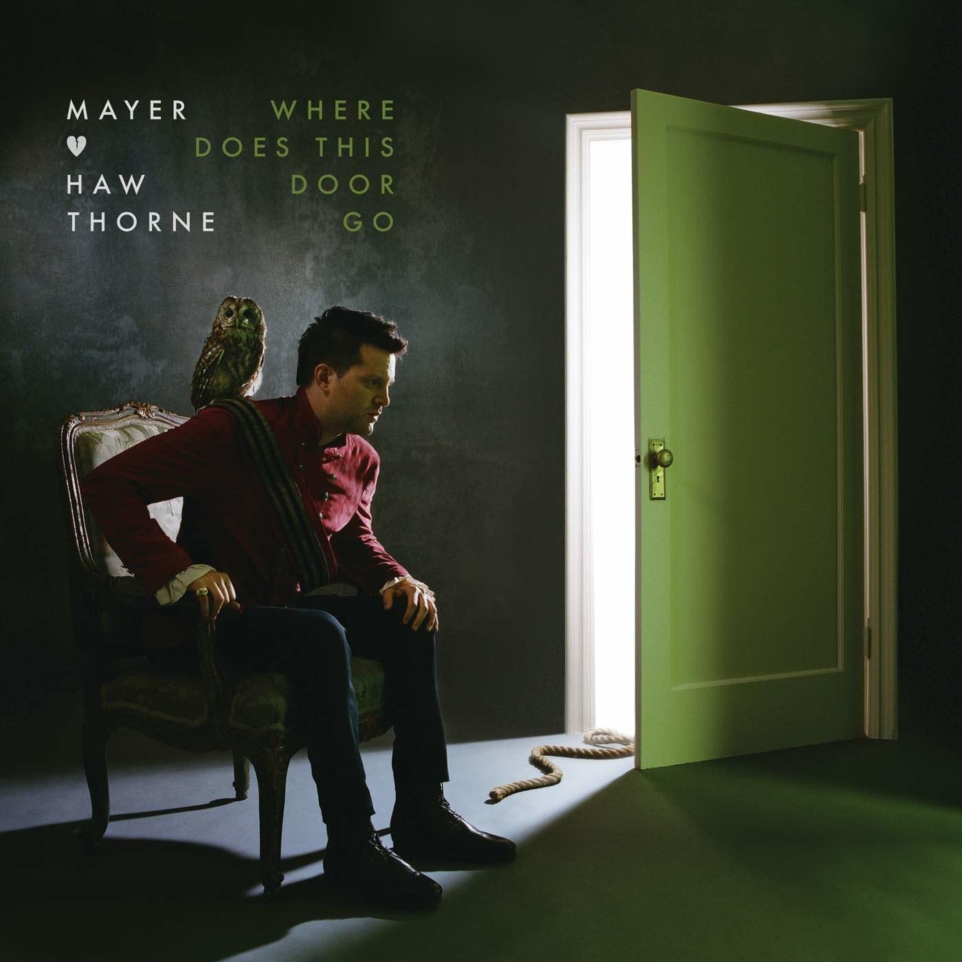 Mayer Hawthorne sitting in front of an open door.