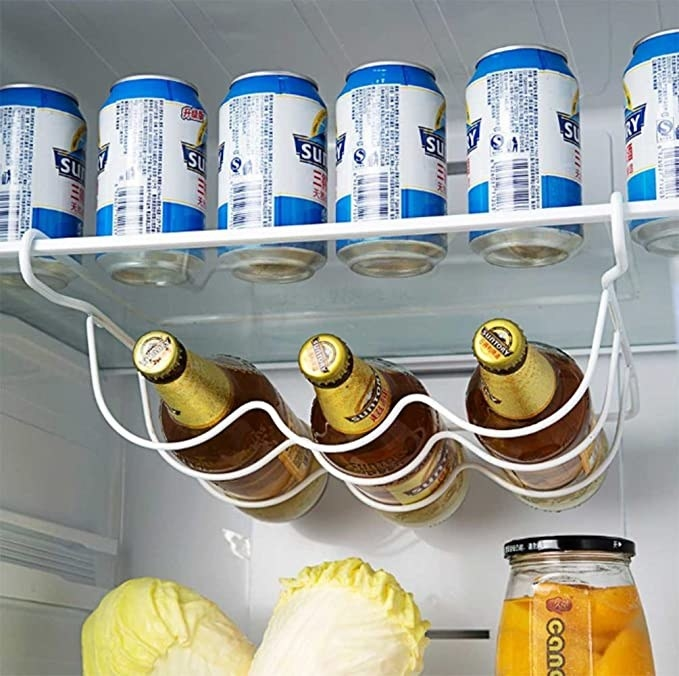 Three bottles of beer placed in the bottle rack, hanging from the fridge shelf.