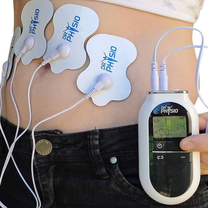 Four adhesive pads stuck to a person's abdomen with the digital controller in their hand.