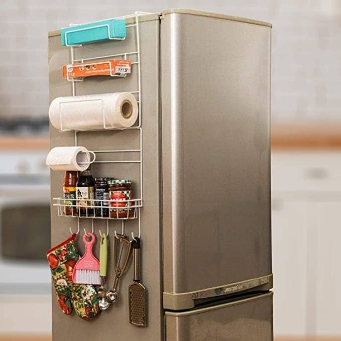 Hanging shelf on the side of the fridge with some kitchen towels, oven mitts and other kitchen products on it.