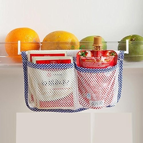 Mesh bag hanging in the fridge with some sauce packets in it.