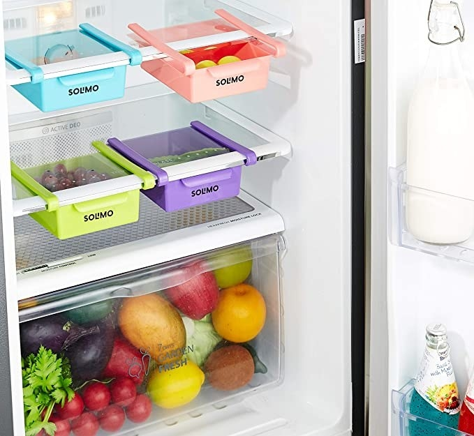Fridge space savers hanging under the shelves with some light fruits and vegetables in them.