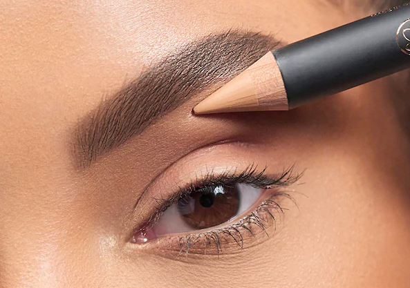 A person applying the product beneath their eyebrow