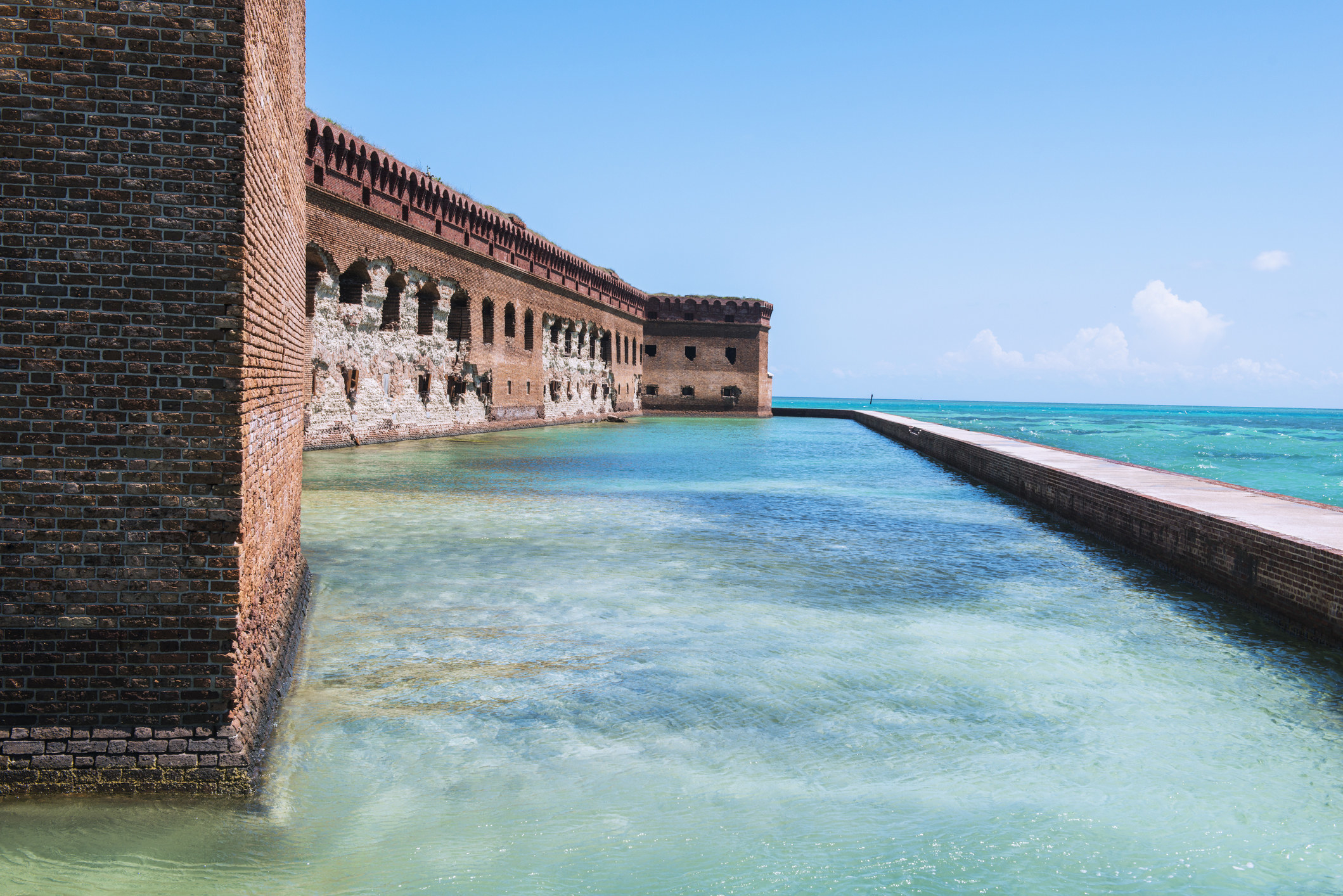 Clear, turquoise waters around a historic brick fortress
