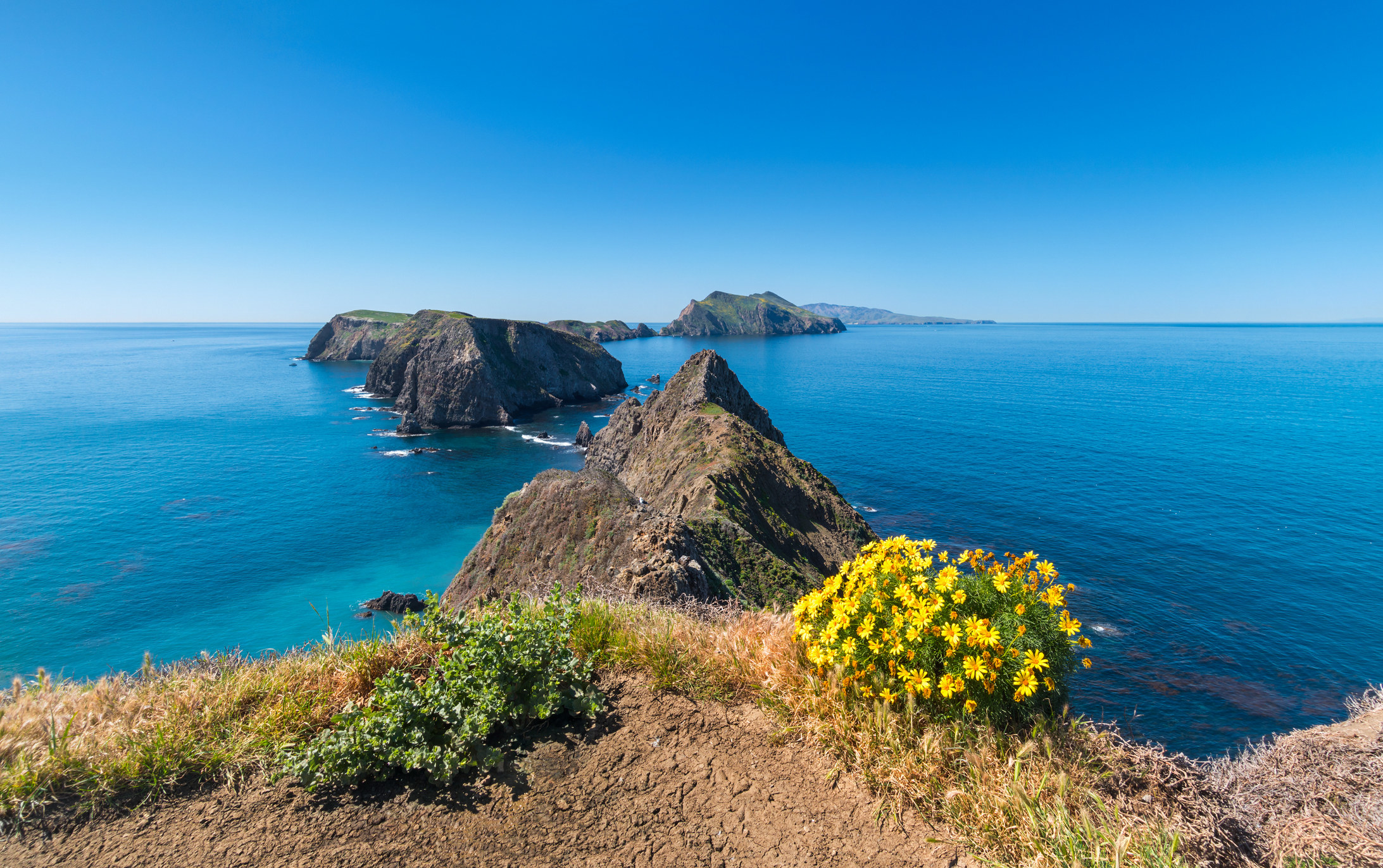 A POV shot overlooking a cliff with rocky islands in the distance, making a chain of islands
