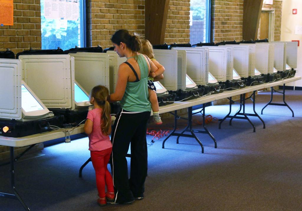 一位母亲在她的两个孩子旁边投球旁边的选票