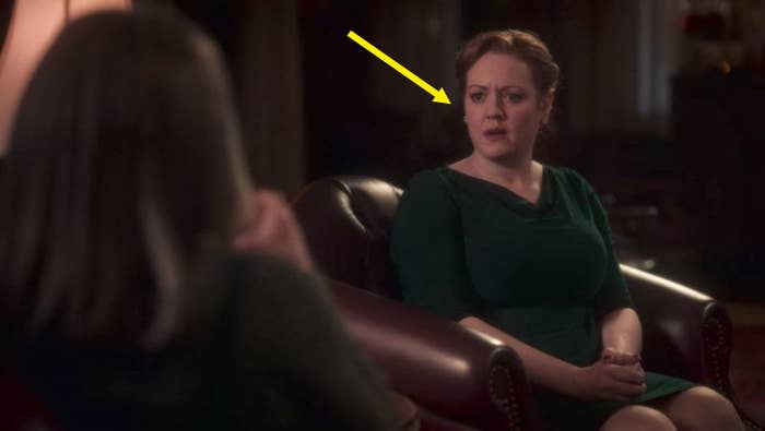 """One of the wedding guests from """"Haunting Of Bly Manor"""" sitting down on a chair; she is wearing a green dress and has blonde hair"""