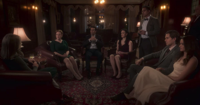 The wedding guests sitting in a circle while listening to a ghost story being told