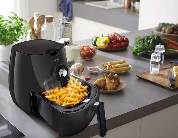 French fries being cooked in the air fryer. Other fried food items like fried chicken, spring rolls are kept next to it.