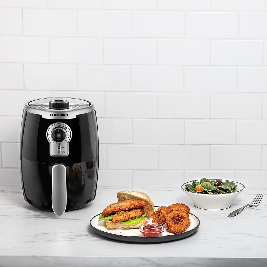 The air fryer next to onion rings and a fried chicken sandwich