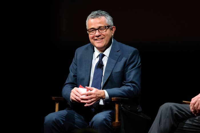 Jeffrey Toobin holding cue cards at an on-stage event.