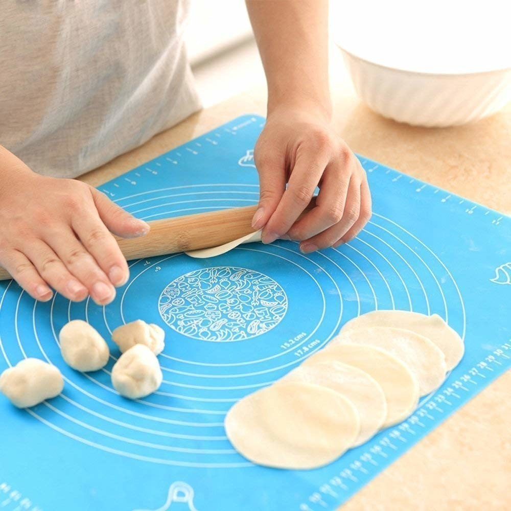 The silicone mat with different circular markings and a person rolling out a small flatbread using the mat's measurements.