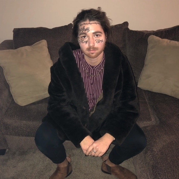 Someone dressed as Post Malone, with a bunch of hand-drawn tattoos on their face