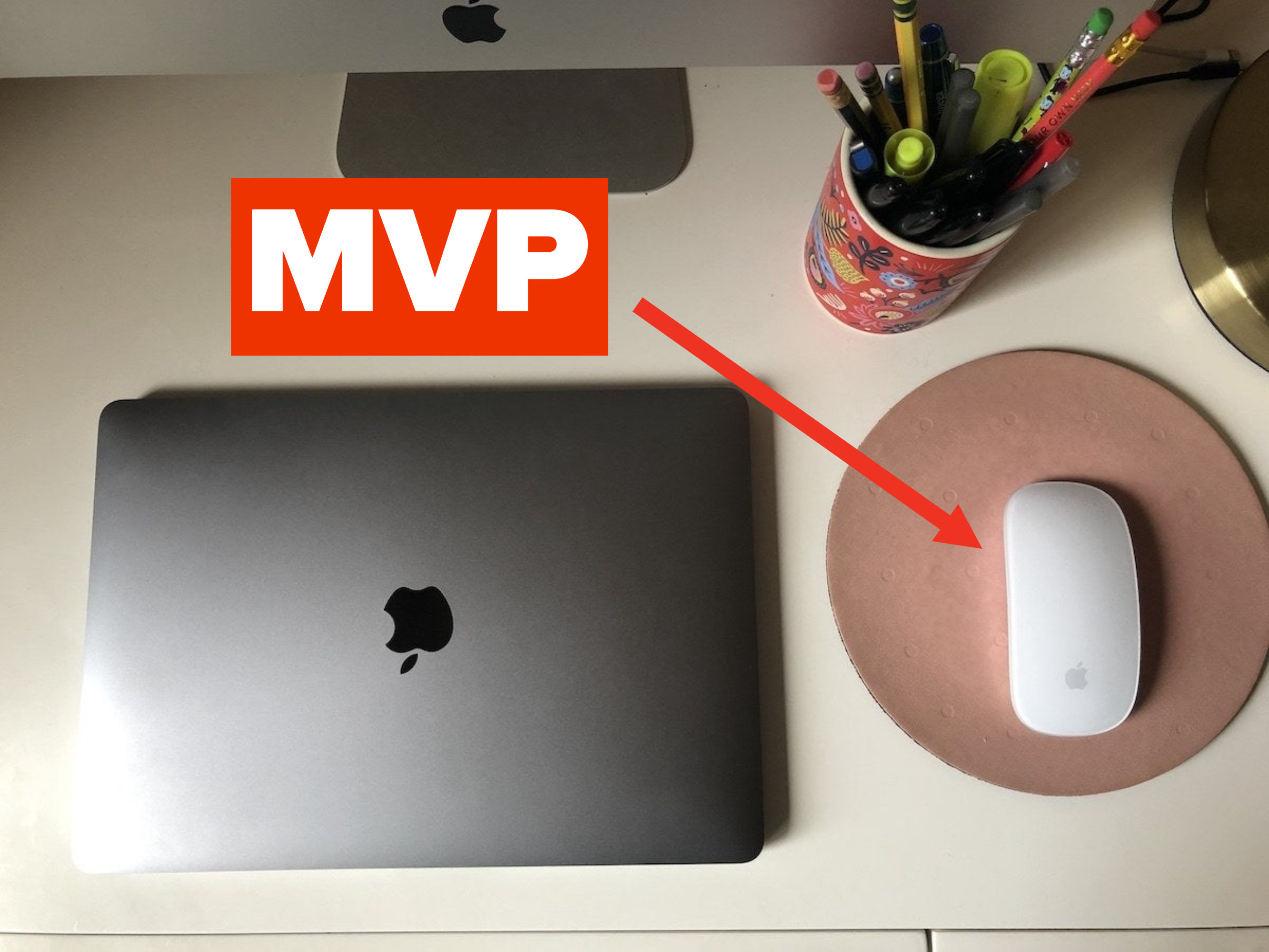 A wireless mouse next to a laptop