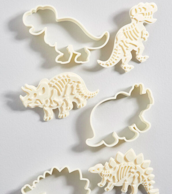 A trio of dinosaur-shaped cookie cutters and a trio of fossil-shaped cookie stamps on a simple background