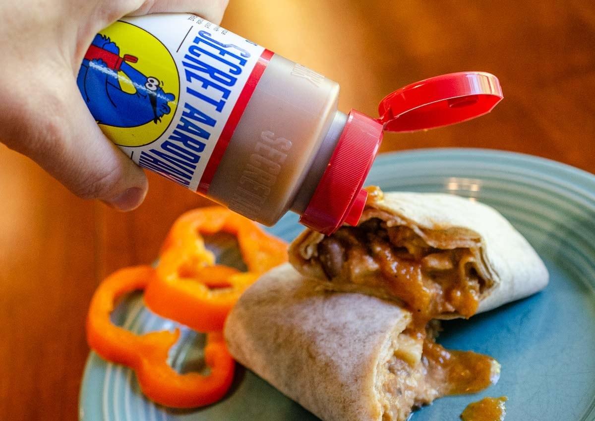 Someone pouring Secret Aardvark habanero hot sauce onto a burrito.