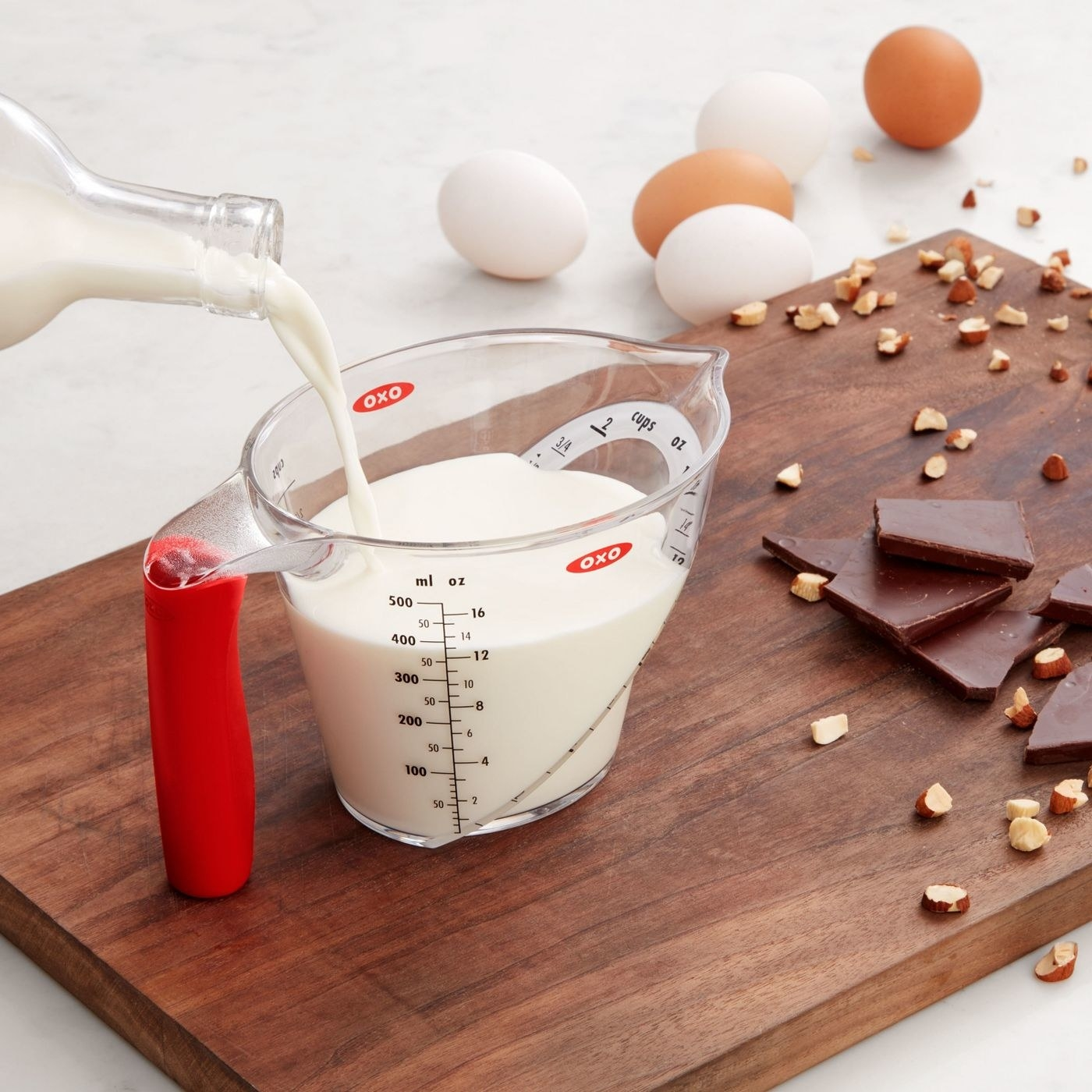 person pouring milk into an angled measuring cup