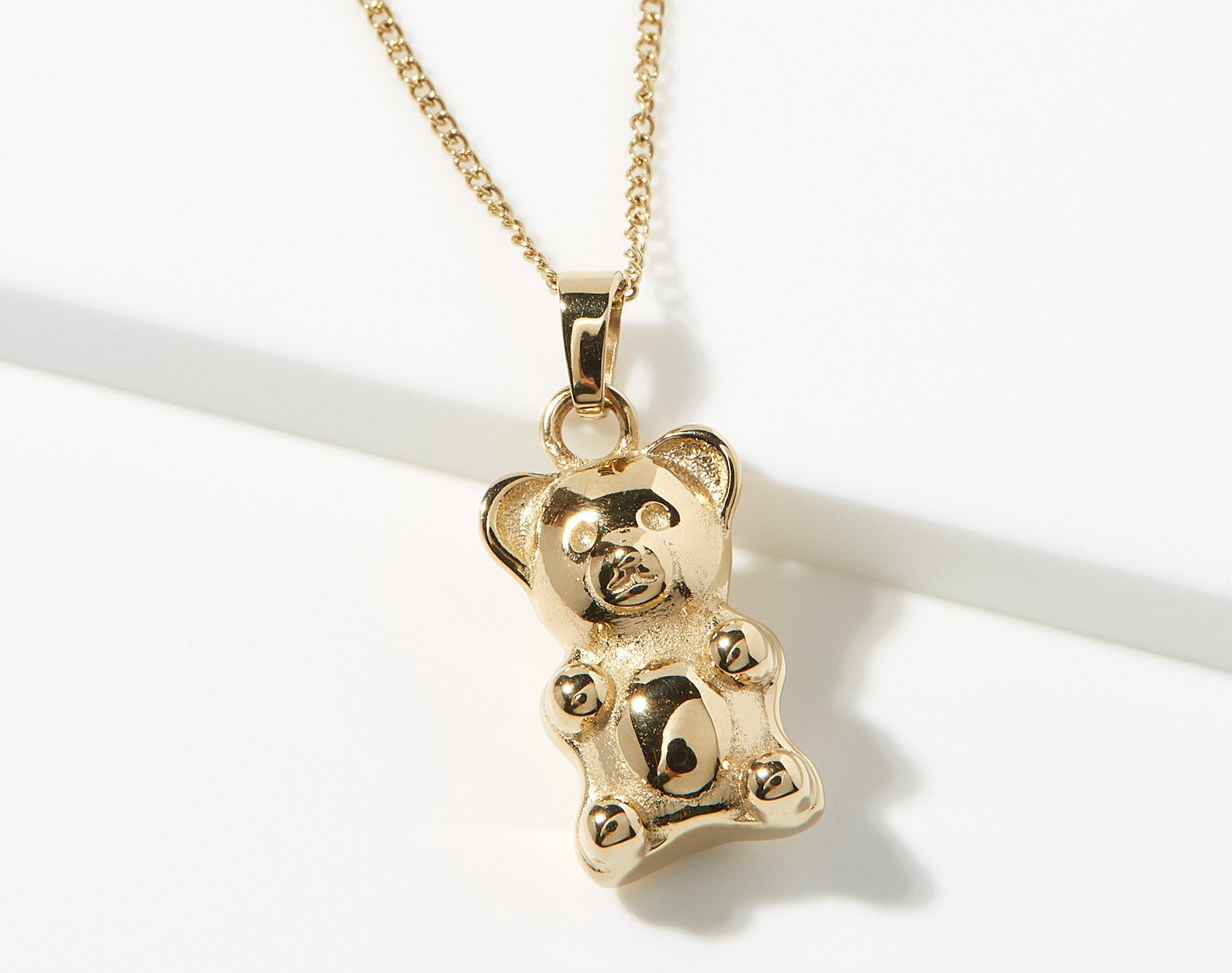A gold necklace with a gummy bear shaped pendant