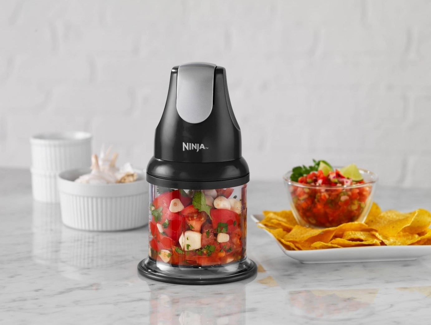 black ninja food chopper on a marble counter top with salsa ingredients in it