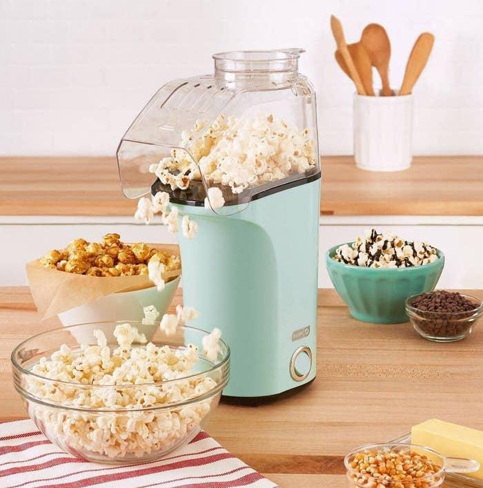 seafoam green popcorn maker popping fresh popcorn into a clear bowl