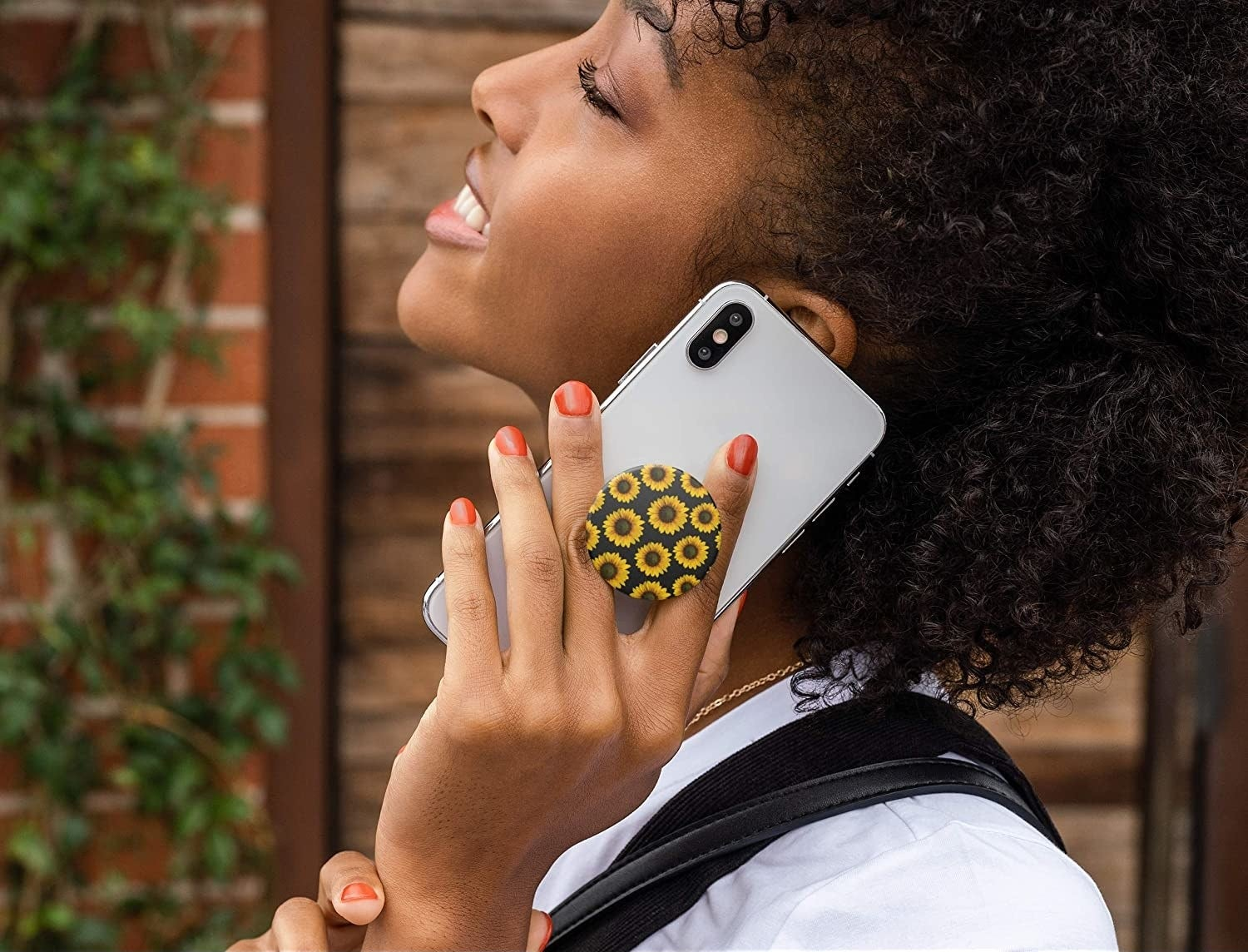 A person holding a phone to their ear that has a phone grip attached to the back